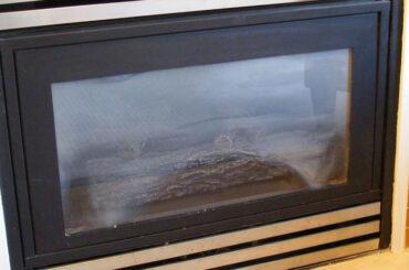 kozy gas fireplace with dirty glass
